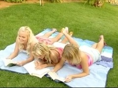 3 pretty blonde girls frolicking on the grass
