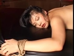 Black haired tied up Asian slut squirts on a table