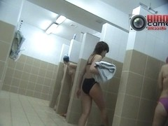 Girls take off their swimsuits in the women's shower