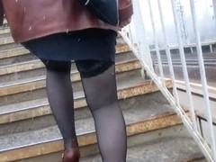 Girl in stockings going upstairs under the snow