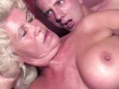 Blonde granny with a super hairy pussy and big, fake tits is fucking a younger guy