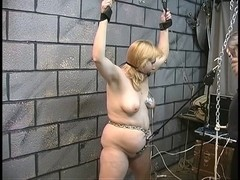 Serf receives tied with leather cuffs and slaver gives her electric shocks in teats