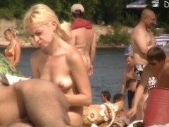 Nude people sunbathing and relax on the shore