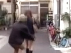 Busy looking Asian babe skirt sharked on a street.