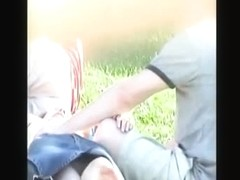 Couples lying on the grass on a picknic and a voyeur taking upskirt videos
