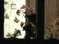 Stunning mature bitch is dressing up by the window