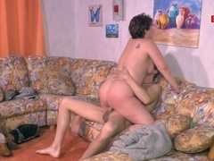 Skinny guy is fucking a slutty, German mature from the back, in her living room