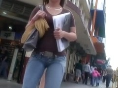 Hot body girl in tight jeans walking the street with a voyeur behind her