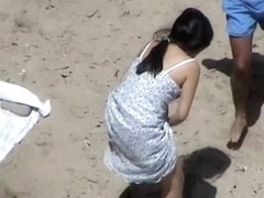 Dark haired woman spied pissing on the beach