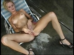 Skinny blond in lounge chair plays with her love button then slips marital-device into her snatch