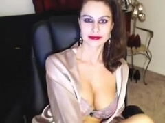 Bosomy webcam milf fingers her throbbing twat on a sofa