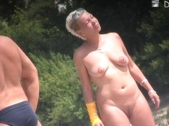 Sexy blonde MILF relaxing on the beach on spy cam