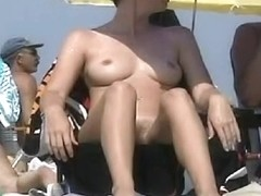 Big breasted coquette sunbathing on a nudist beach