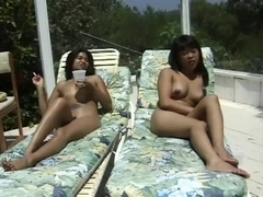A pair of cute tanned Asian babes relax while sunbathing nude