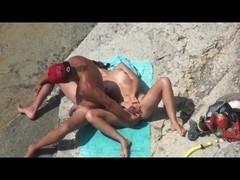 Couple of mutually masturbating to orgasm at a public beach