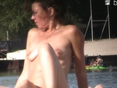 Babe with small tits and shaved vagina relaxes on the beach