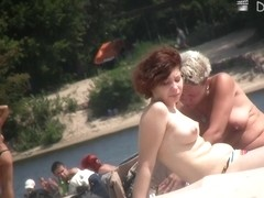 Mature women are relaxing on the beach and caught on cam