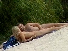 Nude couple chilling on the beach