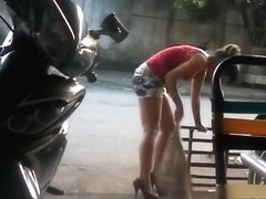 Asian waitress sweeps the street wearing very high heels